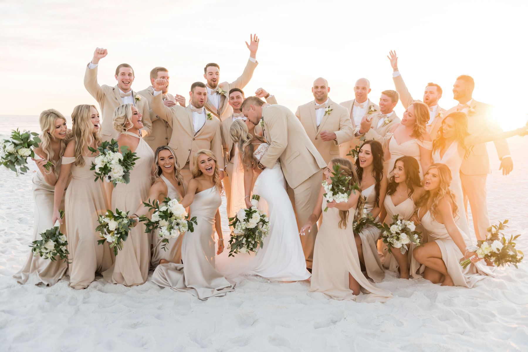 Bride and groom on the beach at sunset with fun wedding party cheering
