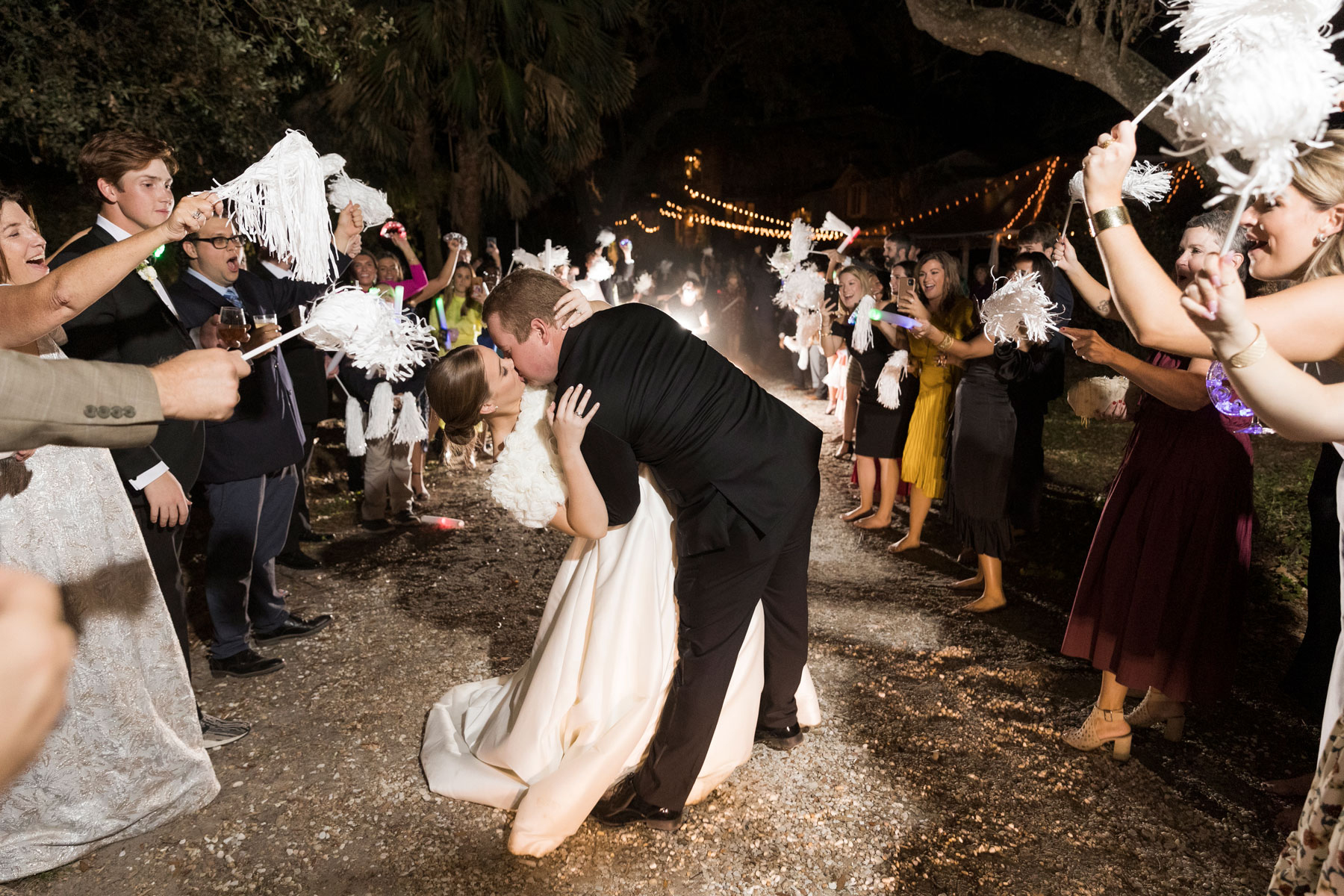 Romantic grand exit photo of the bride and groom kissing in a dip with shakers